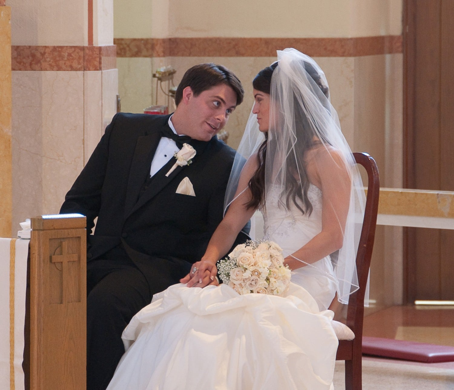 bride and groom talking in church