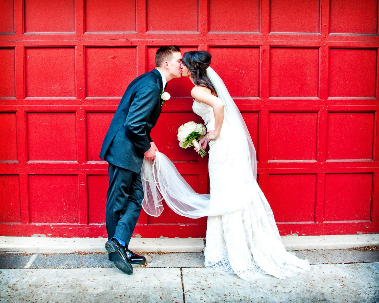 wedding kisses in front of red door
