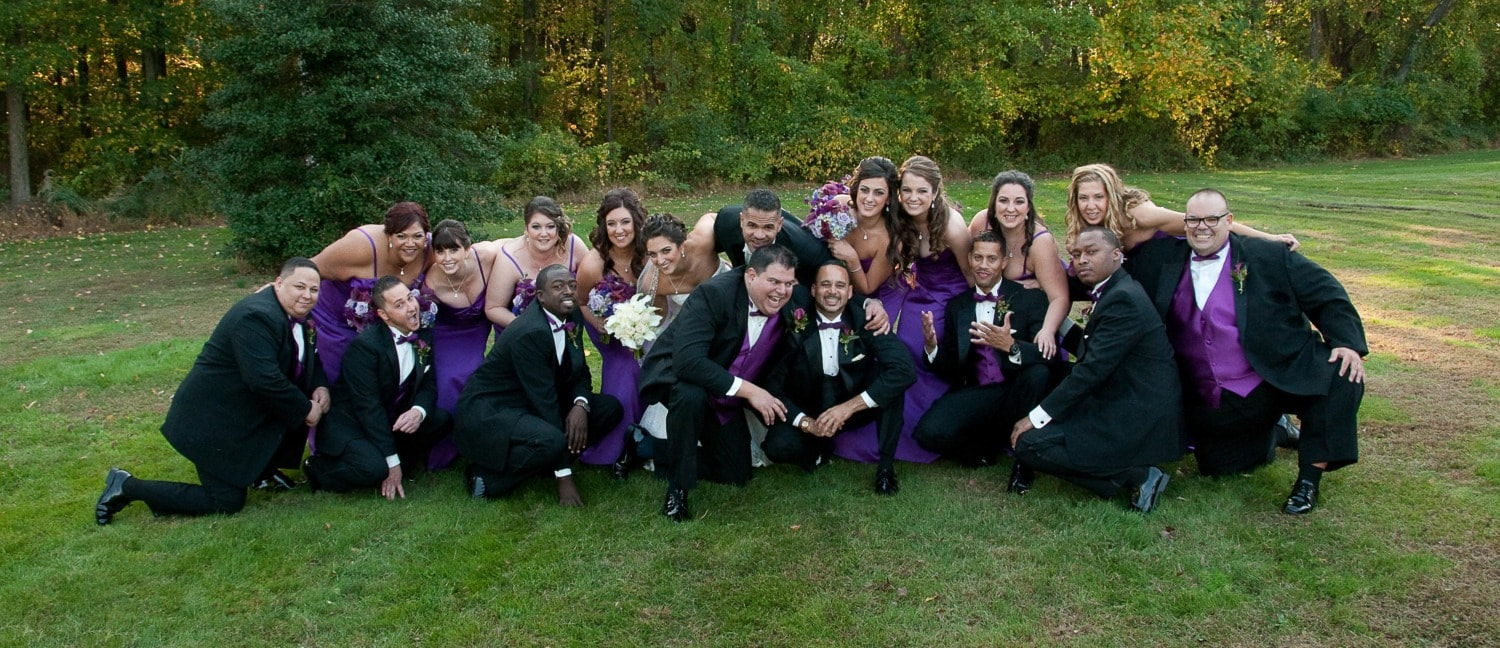large group wedding photo with purple colors