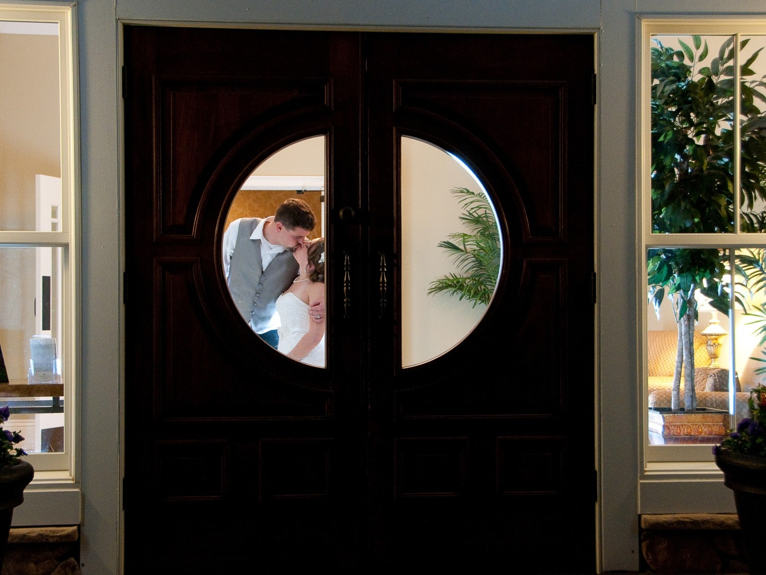man and wife kissing through church doors